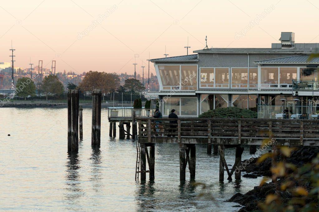 People fishing at sunset at the docks of North Admiral, Seattle, Washington, USA.