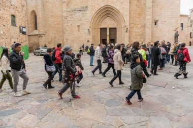 Asian tourists in the Santa Maria square in the old town of Caceres, Extremadura, Spain.