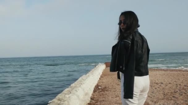 girl in sunglasses in a leather jacket walks against the backdrop of the sea