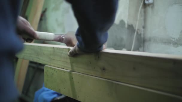 joiner sawing a wooden beam with a japanese saw