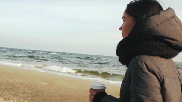 the girl goes along the sea and holds in her hand a disposable cup with a drink