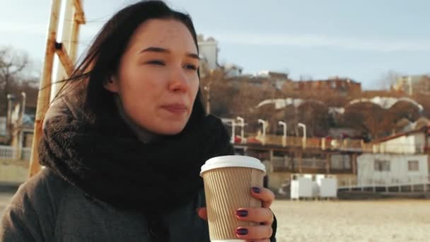 girl holding a disposable cup of coffee and talking