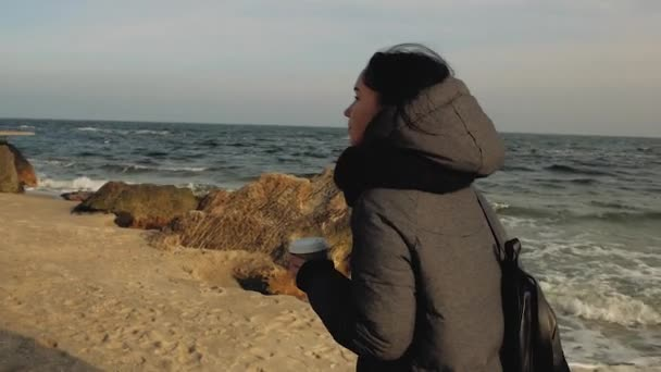 the girl comes to the sea and stones and holds in her hand a disposable cup of tea