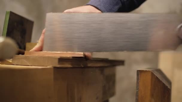 male carpenter sawing wooden element with a hand saw. 4k