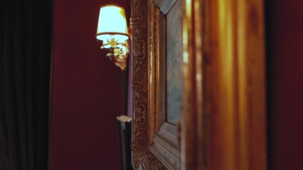 vintage paintings on the wall in a retro frame against the wall lamp