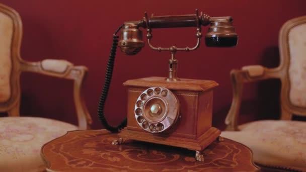 Retro telefon s trubicí na dřevěném stole ve starožitném interiéru