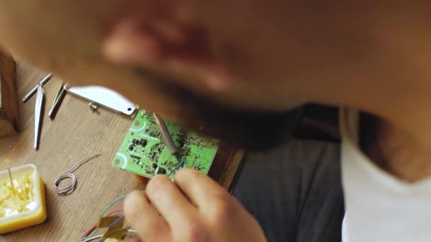 egy elektronikai mérnök forrasztóeszközök egy elektromos tábla processzorokkal. A mester javítások elektromos berendezések. kilátás fentről. 4k videó