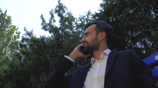 businessman using a mobile phone in a park on a bench. man talking on a cell phone. bearded man talking on a smartphone. young attractive bearded man is sitting and talking on a cell phone with a friend. 4k. 4k video