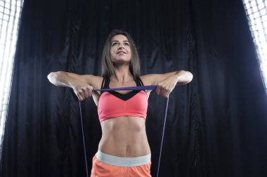 Fitness model in bright sports form shows exercises with elastic band