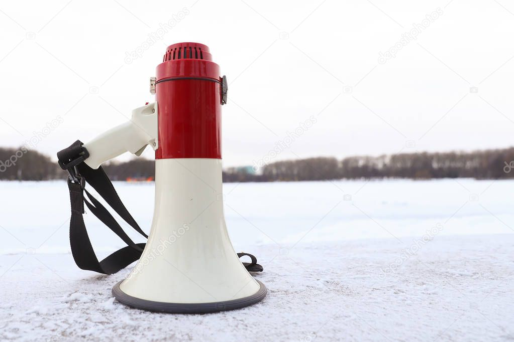 White-red megaphone stands on the shore of a frozen lake