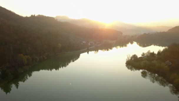 Aerial: Flying over beautiful pond in autumn at evening at sunset. Calm sunny weather with clear water reflecting nature round lake.