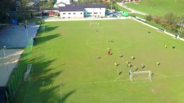 Anténa: Děti hrát fotbal na velké zelené trávě fotbalové hřiště