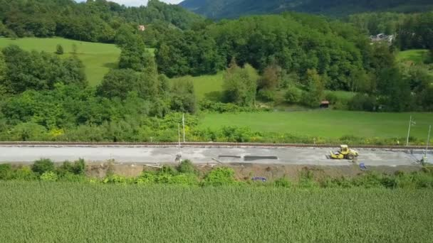 Anténa: Letící podél železnice rekonstrukce webu. Mnoho strojů pracují. Natáčení rekonstrukce koleje na železniční vedle krásné řeky na slunečný den