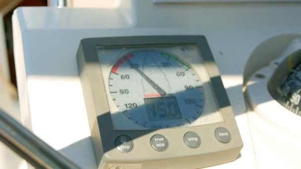 Sailing boats instrument by the steering wheel showing wind direction and speed. Closeup on windex and some rotating blurred steering wheel.