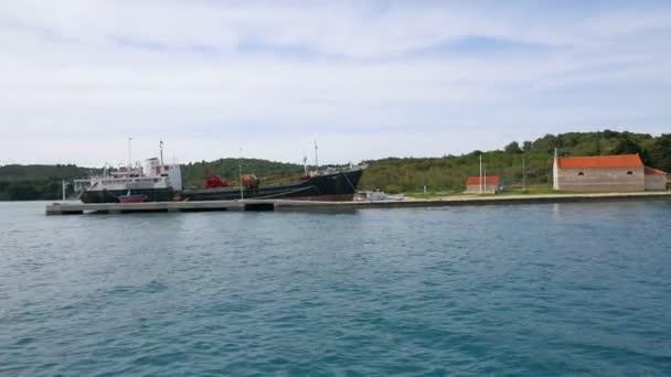Plachtění vedle betonové molo s ukotvený nákladní loď a malý kostelík vedle. Natočeno na plachtění tip v Jaderském moři v pomalém pohybu hd