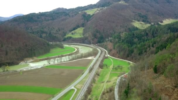 Aerial: Flying over valley with river and railway beside road. Filming beautiful green Slovenian landscapes full of forests.