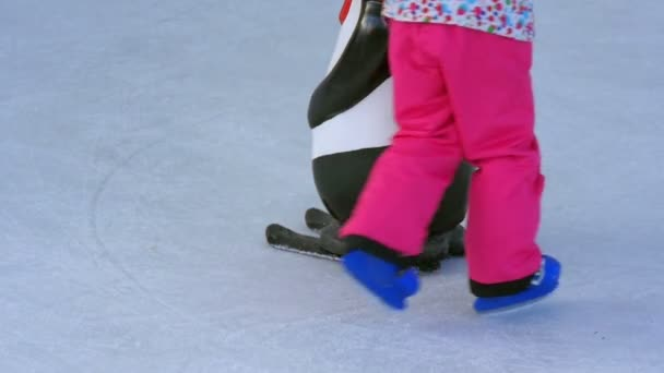 Closeup on kids learning ice skating on artificial ice rink. Learning with help of plastic figures to hold in arms while learning.