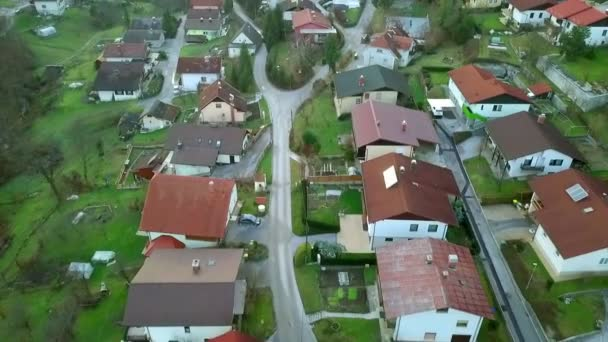 Aerial: Drone flying over small settlement with lots of green surfaces. Quiet neighborhood and few children playing football on playground.