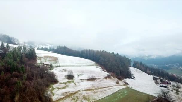 Anténa: Létání na chladného zimního rána směrem k lesní s některými domy v popředí.