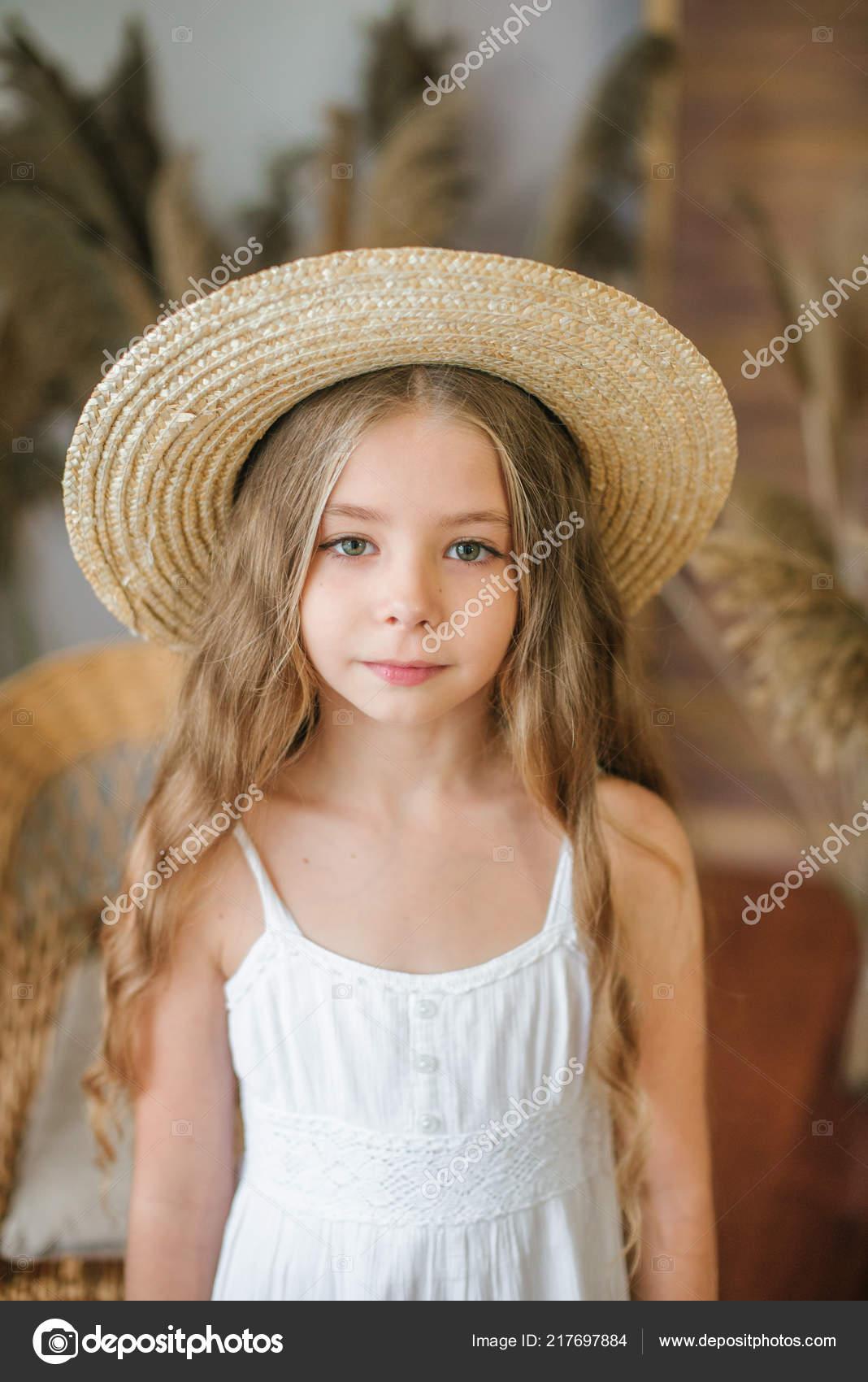 Uma doce menina com longos cabelos loiros em um véu de noiva branco e um  chapéu de palha em uma cadeira de vime e uma decoração de reed — Foto de  Capable97 a2ae424914d