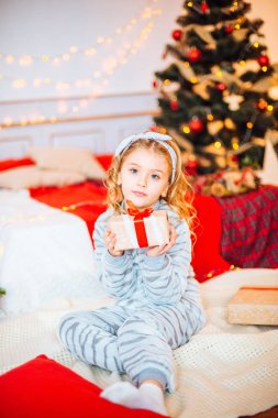Little girl in pajamas at Christmas morning.Merry Christmas.Little girl rejoices to the Christmas gift
