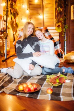 Red-haired teen girl and her mom in the studio in the fall scenery with yellow leaves, blankets, apples and pumpkins