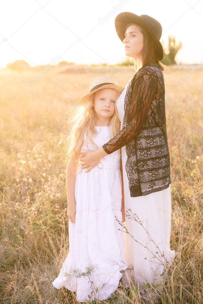 A girl in a white dress and straw hat with blond long hair with an older sister in the summer in a field at sunset on a sunny day