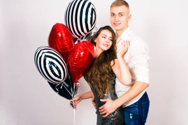 Kissing couple posing on grey background with balloons heart. Valentine's day. - Image