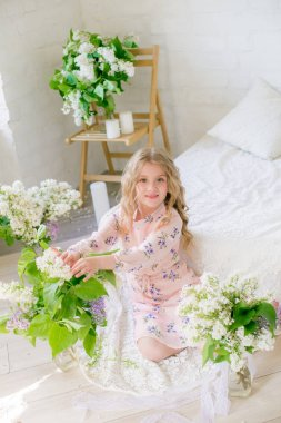 Cute little girl with blond hair in a beautiful dress in a spring studio with lilac flowers