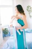 Junge Mutter und kleines süßes Baby zu Hause auf dem Bett mit blauer Tagesdecke und Kissen