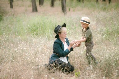 Little boy in a hat and his mom in the park in summer at sunset