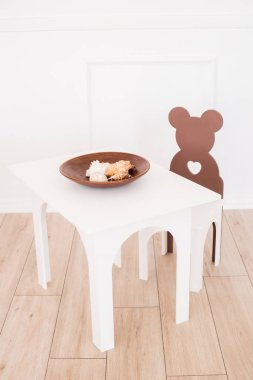 A cute white children's table with a chair, a bear with sea shells on it. Furniture for a children's room