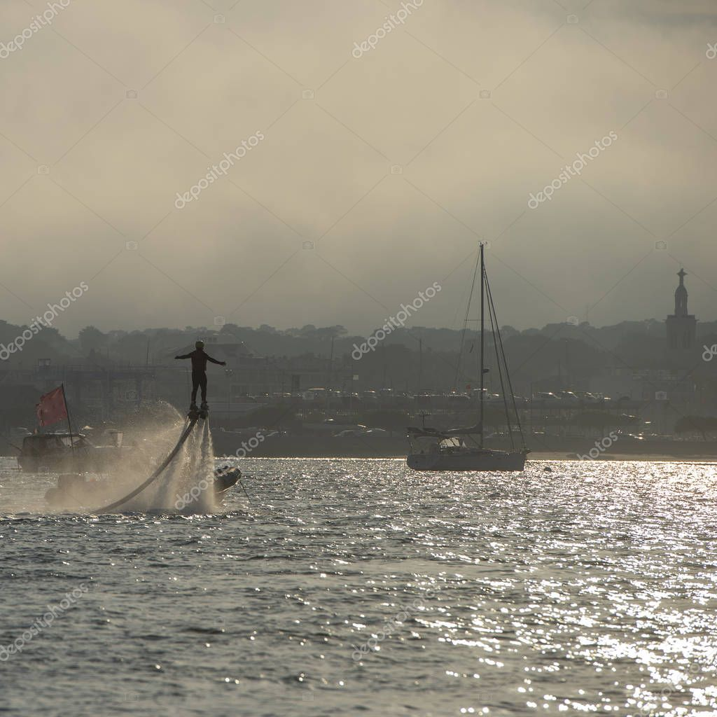 Man demonstrates fly board acrobatics while flying on aquaflyer water jetpack at Arcachon, France, Europe