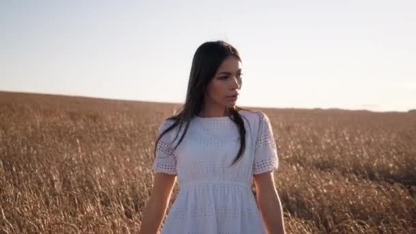Egy fehér ruhás lány sétál át a búzamezőn a naplemente hátterében.