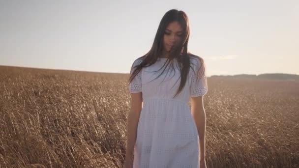 Egy fehér ruhás fiatal lány sétál a búzamezőn, és a kamerába néz.