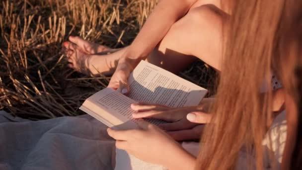 Nők kezei összezárva lapozgatják egy könyv lapjait a lenyugvó napon egy mezőn.