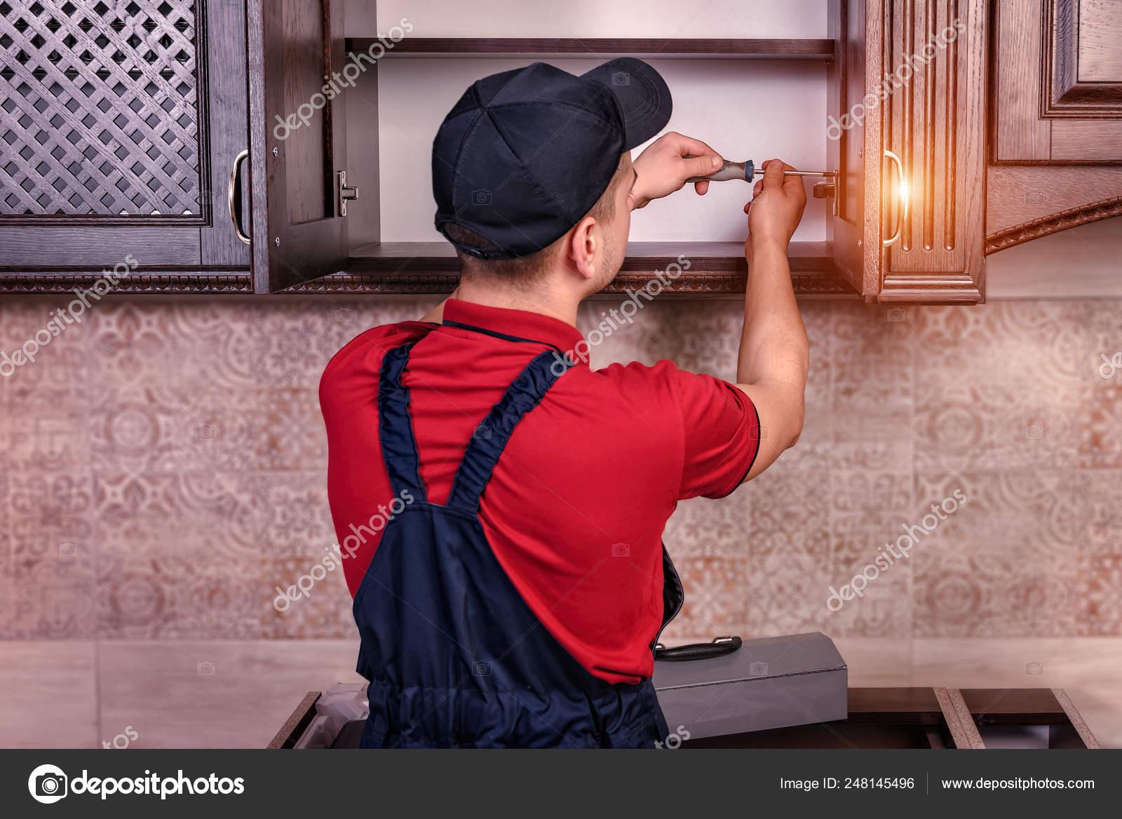 Un trabajador joven es montar muebles de cocina madera ...