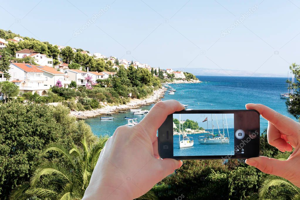 Taking a photo of the Croatian coast landscape and Adriatic sea with a smart phone. Photo on screen and picturesque scenery in background.