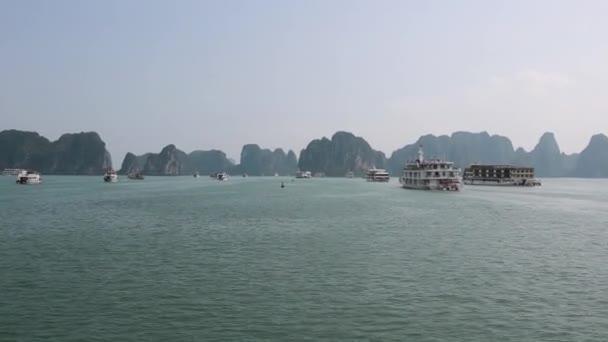 Sightseeing cruise boats sailing towards karst island formations of Ha Long Bay, Vietnam. Long shot.