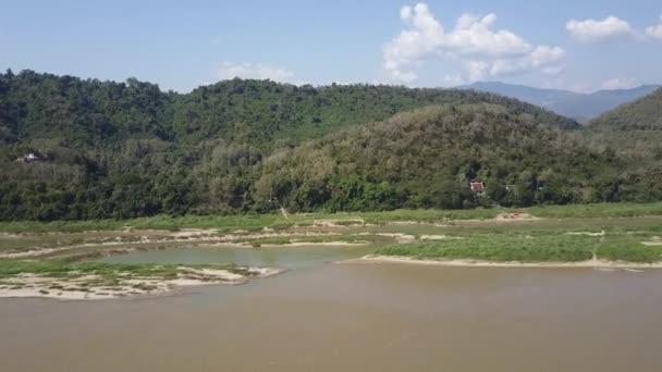 Hornatá krajina s bujnou vegetací podél břehů řeky Mekong v Laosu. Vyhlídkové lodní plachty níže. Letecký snímek