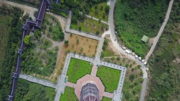 Buddhist temple grounds filmed from directly above. Bai Ding temple buildings, the pagoda, and their terrain seen from the sky. Overhead shot. Drone shot.