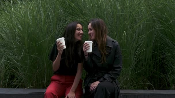 Two girlfriends drinking coffee and smiling seated outdoors. Three quarter length.