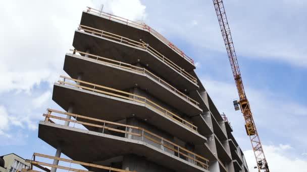 Stavební jeřáb nad budovou ve výstavbě