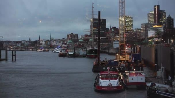 Yachten und Boote auf der Elbe mit Hamburger Bauten in der Abenddämmerung
