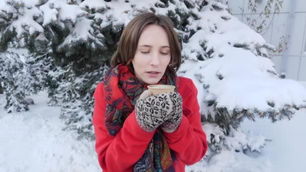 Vonzó gyönyörű lány, aki iszik forró teát vagy kávét a télen az utcán, ő visel kötött ujjatlan áll közelében karácsonyfa piros kabát