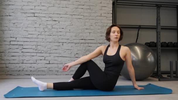 Seitenansicht Yogamatte junge athletische Frau dehnt Hüfte, Oberschenkelmuskeln, Beinmuskeln drinnen in einem Fitnessstudio. Dehnübungen