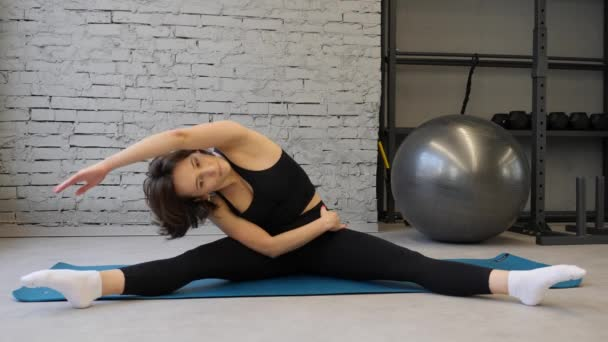 Yoga mat young athletic woman stretching hip, hamstring muscles, leg muscles indoors in a gym. Stretching exercises
