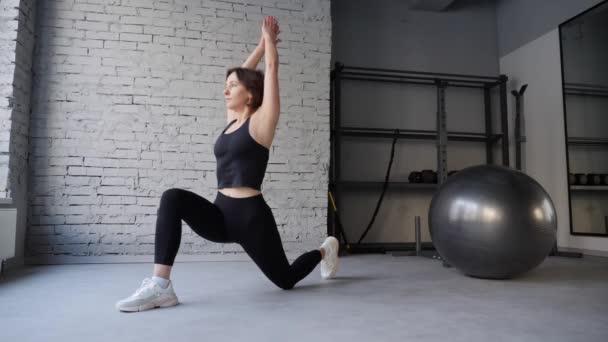 Yogamatte junge athletische Frau dehnt Hüfte, Achillessehne, Beinmuskeln in einem Fitnessstudio. Dehnübungen