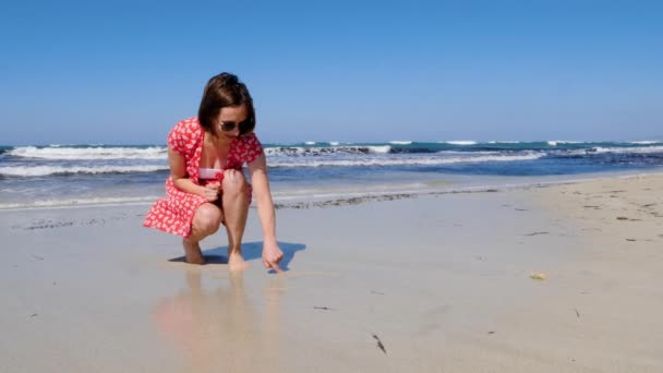 Young attractive woman drawing heart sign on a lonely sandy beach with strong waves hitting the shore. She wears red dress and sunglasses. Slow motion