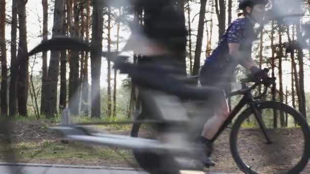 Young fit cyclist woman starts pedaling bicycle. Road cycling. Triathlon concept. Slow motion